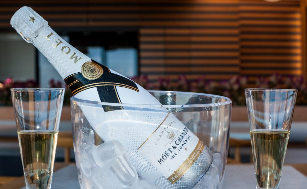 A bottle of champagne and two elegant glasses filled with the tasteful drink served at Basil' Honey Restaurant.